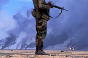 KUWAIT. 1991. Safwan. US soldier in front of oil wells in fire.