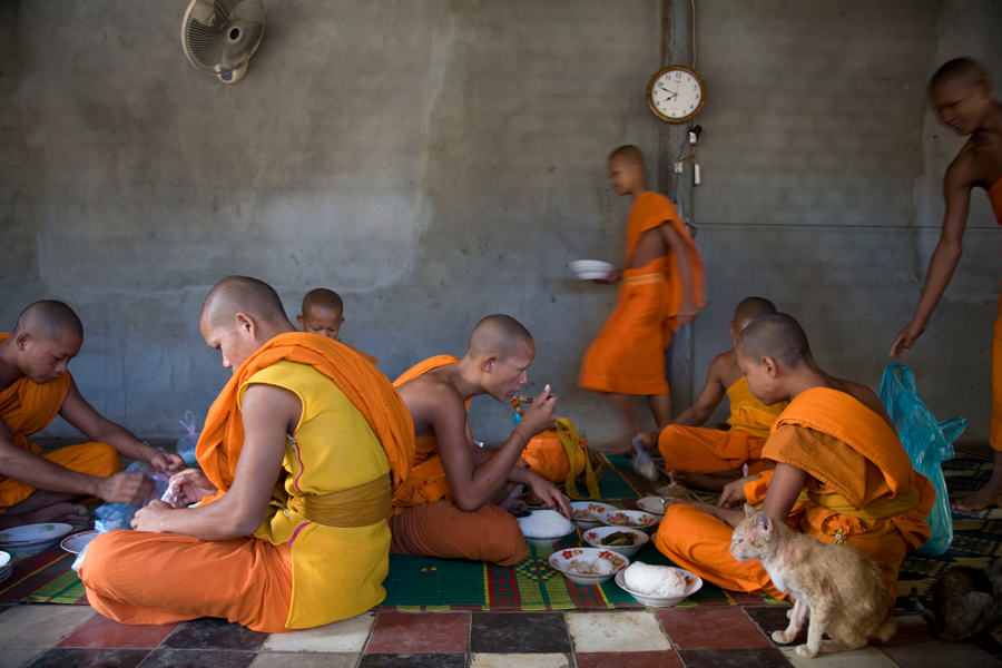 CAMBODIA. Siem Reap.  Young monks eat lunch in wat Po Bun Thiay Jai.
